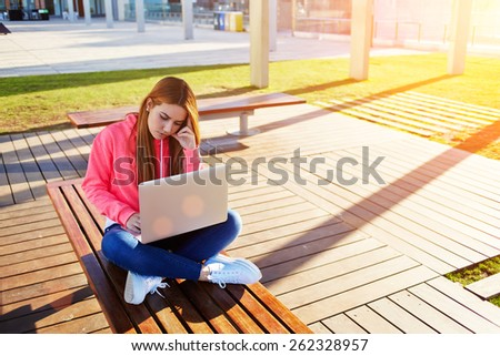 Gorgeous blonde hair female student focused and busy using laptop computer at campus, charming female teenager studying for exam on park bench with open net-book and big copy space for text, flare sun - stock photo