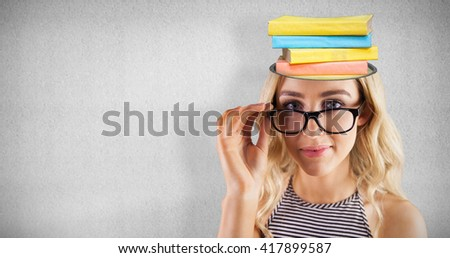Gorgeous blonde hipster posing with glasses against grey wall - stock photo