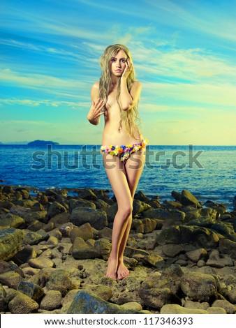 Gorgeous blonde in a flower bikini on the shore blue sea - stock photo