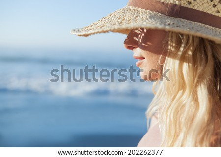 Gorgeous blonde in straw hat smiling on beach on a sunny day - stock photo