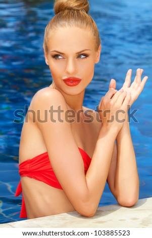 Gorgeous blonde lady in a red bikini standing in the water at the edge of a pool enjoying the sun - stock photo