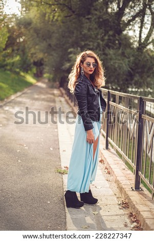 Gorgeous blonde posing in a sexy light blue dress tight and fluid on her body. Fashion shoot of beautiful woman at the river side with sun in her  hair - stock photo