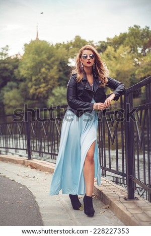 Gorgeous blonde posing in a sexy light blue dress tight and fluid on her body. Fashion shoot of beautiful woman at the river side sitting with an arm on the fence - stock photo