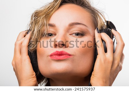 Gorgeous blonde posing on light background. Girl in stereo headphones. Young blond woman listening to music on headphones. - stock photo