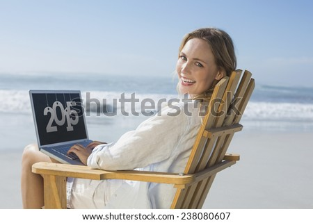 Gorgeous blonde sitting on deck chair using laptop on beach against 2015 - stock photo
