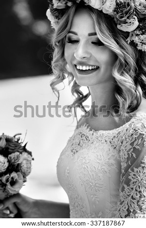 Gorgeous blonde smiling emotional bride in vintage white dress in wreath b&w close-up - stock photo