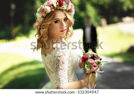 Gorgeous blonde smiling emotional bride in vintage white dress in wreath close-up - stock photo