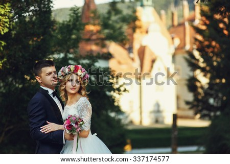 Gorgeous blonde young bride and charming groom posing at sunset  - stock photo