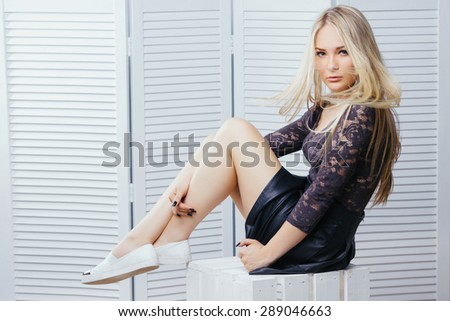 Gorgeous blonde young girl in a black skirt, lace top and white shoes sitting on white wooden box. On a white paravent background. - stock photo