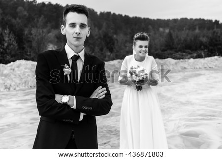 gorgeous bride and stylish groom holding hands and looking at sandy beach lake, black and white photo, luxury wedding - stock photo