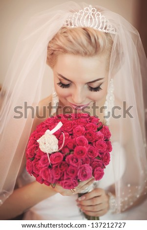 Gorgeous bride blonde with wedding bouquet makeup and hairstyle in bridal dress diamond jewelry at home waiting for groom. Jewelry and beauty. Rich happy girl  have final preparation for wedding - stock photo