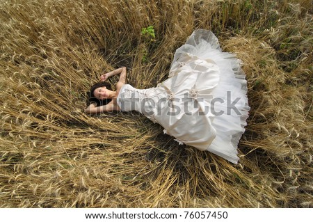 Gorgeous bride is laying in a wheat field - stock photo