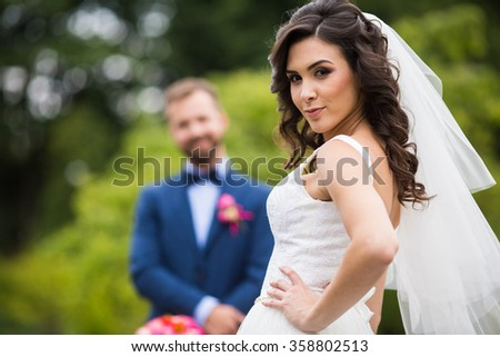 Gorgeous brunette bride in elegant dress posing in the park with groom in the background - stock photo