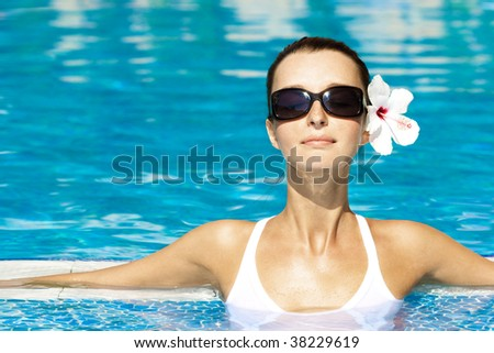 gorgeous brunette enjoying the sun in pool - stock photo