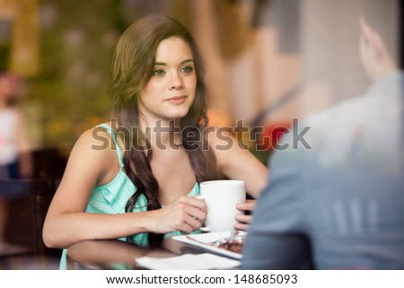 Gorgeous brunette having coffee with a male friend at cafe - stock photo