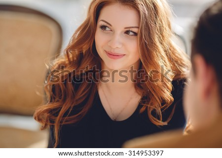 Gorgeous brunette having coffee with a male friend at cafe. beautiful young woman speaks with the man in cafe - stock photo