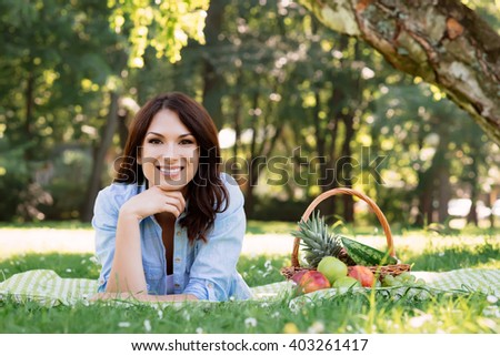 Gorgeous brunette lying on a mat with basket full of fruits in the park. - stock photo