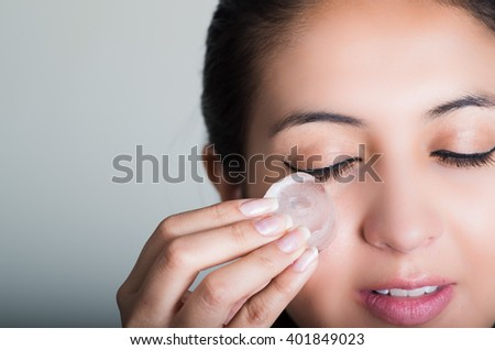 Gorgeous brunette model rubbing ice cube against cheek underneath eye, grey background - stock photo
