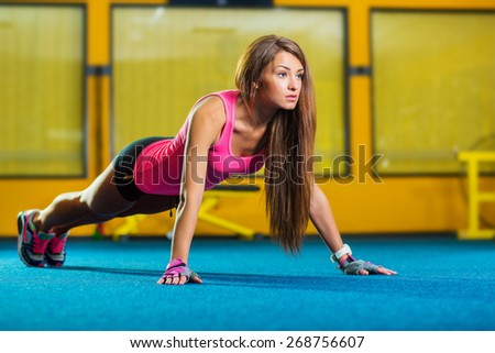 Gorgeous brunette warming up and doing some push ups a the gym - stock photo