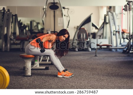 Gorgeous brunette working on her biceps in a gym. Caucasian female model. - stock photo