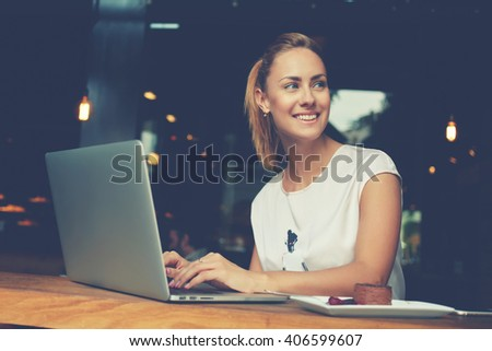 Gorgeous cheerful woman freelancer with good mood using laptop computer for distance work during lunch in cafe bar, attractive female with beautiful smile sitting with portable net-book in coffee shop - stock photo