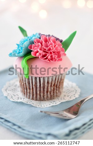 Gorgeous cupcake topped with flowers  - stock photo