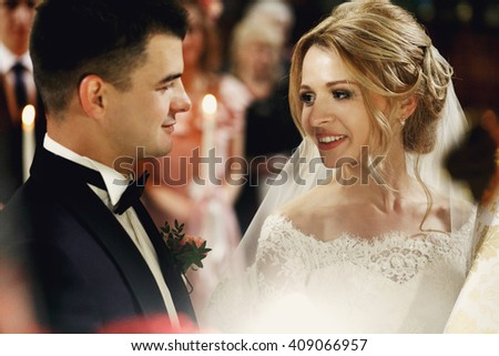 Gorgeous emotional blonde bride looking at handsome young groom in church - stock photo