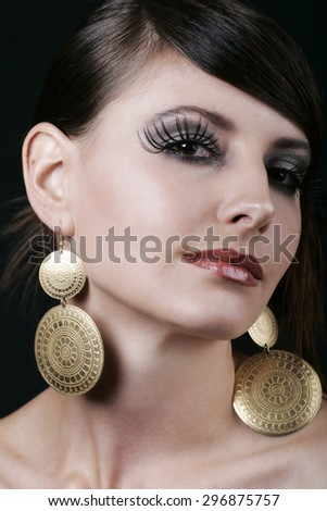 Gorgeous Face of a Young Woman with Makeup and Big Earrings, Looking at the Camera Against Black Background. - stock photo