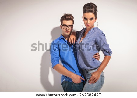 Gorgeous fashion woman posing with her lover on greu studio background. - stock photo