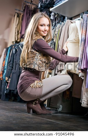 Gorgeous fashionable young brunette shopping around for new clothes. - stock photo