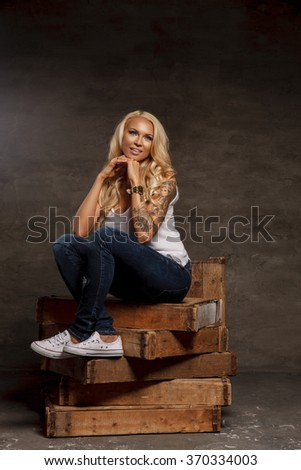 Gorgeous female in denim jeans with blond curly hair. - stock photo