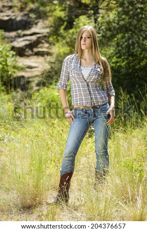 Gorgeous female model posing outdoors in jeans and flannel shirt - stock photo