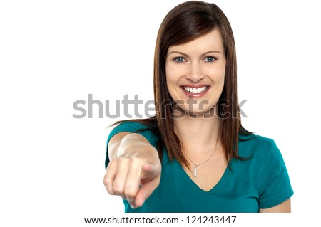 Gorgeous female pointing towards the camera and flashing a smile. - stock photo
