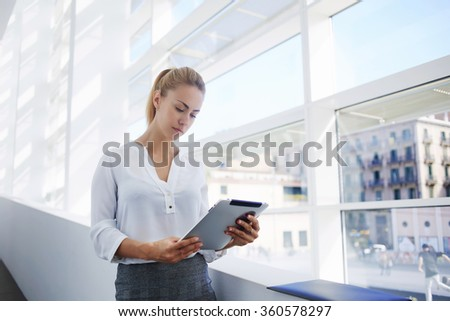 Gorgeous female proud ceo analyzing project on digital tablet while standing near big office window in hall, elegant successful woman employee working on touch pad before important conference - stock photo