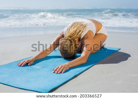 Gorgeous fit blonde in childs pose on the beach on a sunny day - stock photo
