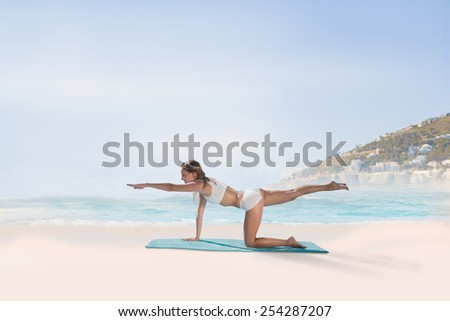 Gorgeous fit blonde in pilates pose on the beach against beautiful beach and blue sky - stock photo