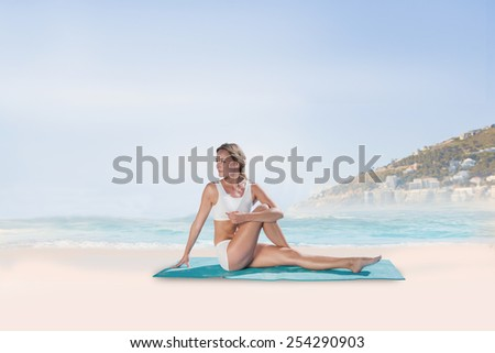 Gorgeous fit blonde in seated yoga pose against beautiful beach and blue sky - stock photo