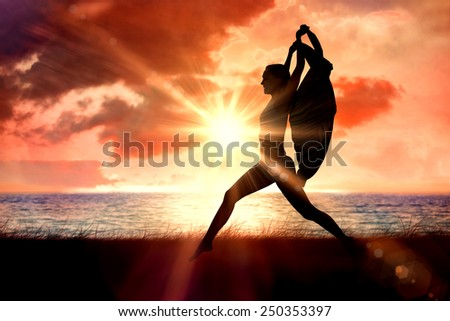 Gorgeous fit blonde leaping with scarf against sunrise over magical sea - stock photo