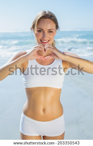 Gorgeous fit blonde making heart shape with hands by the sea on a sunny day - stock photo