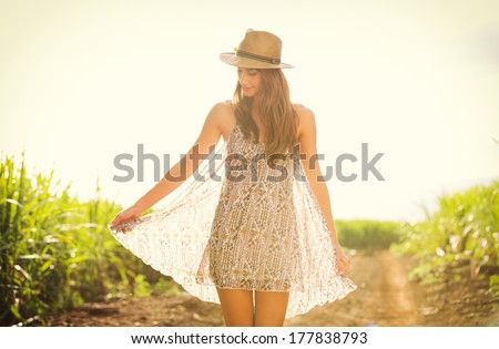 Gorgeous girl walking in the field.  Happy, carefree summer lifestyle.  Woman wearing stylish sun dress.  - stock photo