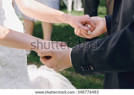 gorgeous happy brunette bride and elegant stylish groom exchange wedding rings on the background of arch - stock photo