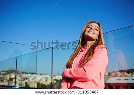 Gorgeous happy female with brightly smile on her face standing against the sky background with copy space for your text message or advertising content,young woman enjoying sunny day outdoors in spring - stock photo