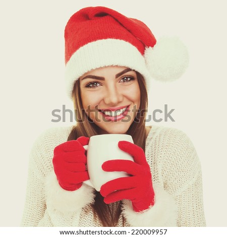 Gorgeous happy Santa girl with white mug. Beautiful Caucasian teenage girl smiling wearing red knitted hat and gloves drinking tea. Instant filter. Square format. - stock photo