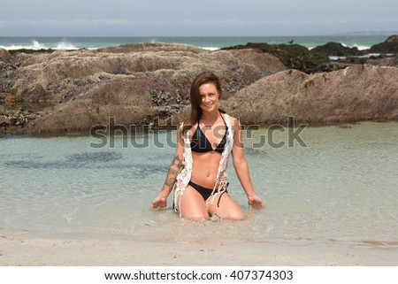 Gorgeous,happy woman with tattoo in a bikini sitting in the sea looking at the camera - stock photo