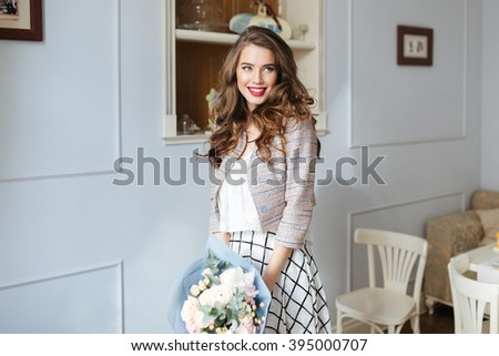 Gorgeous happy young woman with bouquet of flowers standing and smiling in cafe  - stock photo