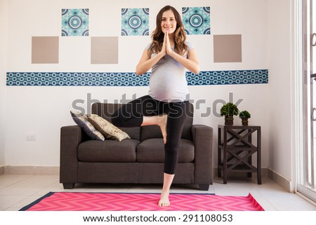 Gorgeous Hispanic pregnant woman doing some yoga at home and smiling - stock photo