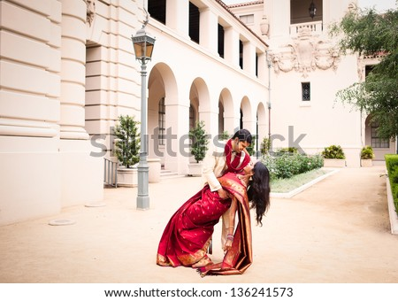 Gorgeous Indian bride and groom in a dramatic pose - stock photo