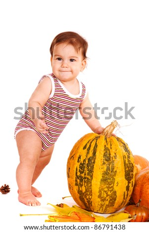 Gorgeous kid standing beside autumnal harvest - stock photo