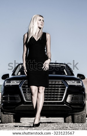 Gorgeous lady at the background of the modern luxury car - stock photo