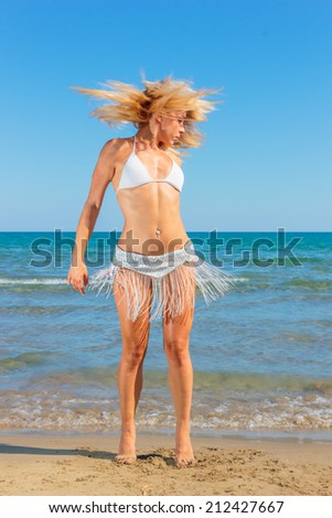Gorgeous lady in bikini dancing on the beach - stock photo